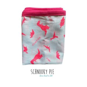 While muslin blanket with pink origami dinosaurs printed all over and a pink binding